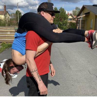 Sonya ja Olli-Pekka harjoittelevat eukonkantokisaan, jossa mies kantaa naista harteillaan.
