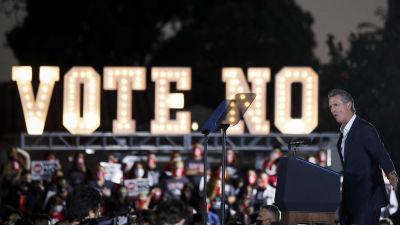 """Kaliforniens guvernör håller tal, i bakgrunden syns en stor skylt där det står """"rösta nej"""""""