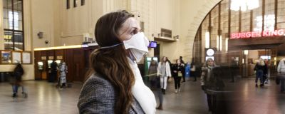 En kvinna med ansiktsskydd står på järnvägsstationen i Helsingfors.