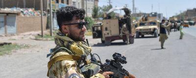 En soldat med pistol bevakar en stad i Afghanistan.
