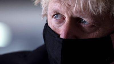 Storbritanniens premiärminister Boris Johnson i närbild. Han bär ett svart munskydd.