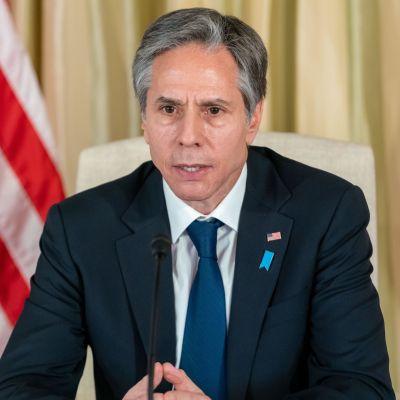 Antony Blinken, USA:s utrikesminister sitter vid ett bord och talar in i en mikrofon i samband med en presskonferens. I bakgrunden syns USA:s flagga.