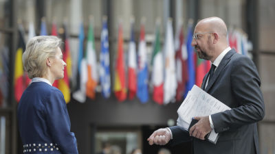 Man och kvinna står vända mot varandra. I bakgrunden europeiska länders flaggor.