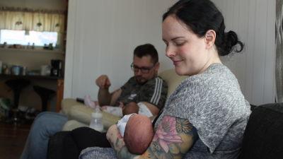 Kvinna som sitter i soffan med ett spädbarn i famnen, i bakgrunden sitter en man med ett annat spädbarn i famnen.