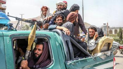 Talibanern med vapen och telefoner i händerna sitter på ett flak.