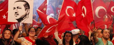 """En folkmassa viftar med Turkiets röda flagga. En person håller upp president Erdoğans porträtt med texten """"Demokratins stjärna""""."""
