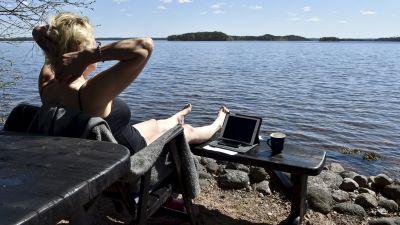 En kvinna sitter och jobbar vid en strand.
