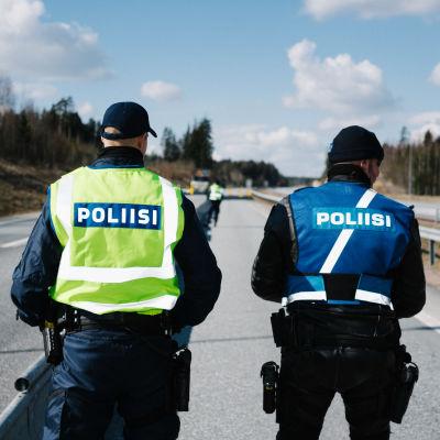 Två poliser i uniform fotograferade bakifrån medan de står på en väg.