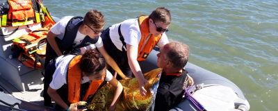 En man har fallit i vattnet i en av övningarna och ungdomarna hjälper honom.
