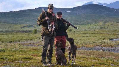 Mies ja nainen riistametsällä metsästyskoirien kanssa.