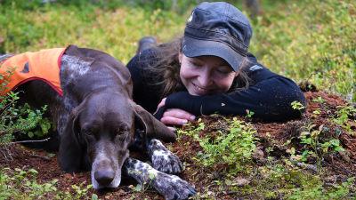 Metsästyskoira ja nainen makaamassa mustikanvarpujen keskellä.