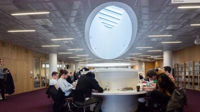 Studerande sitter och studerar i Helsingfors universitets huvudbibliotek.