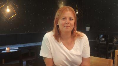 Porträtt på Ida-Maria Pekkarinen iklädd en vit t-skjorta mot en mörk bakgrund.