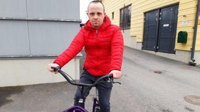 Man i orange jacka på cykel.
