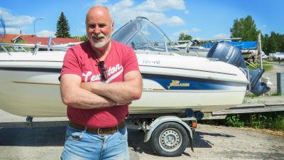 En man står framför sin båt som han har på en båttrailer. Trailern är fast i en större personbil. Sommar och soligt. Mannen har armarna i kors framför bröstet och ser nöjd ut.
