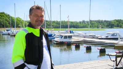 En man klädd i typiska arbetskläder i mörkblått och neon står framför en brygg med förtöjda båtar. Han ler och ser glad ut. Sommar och soligt.