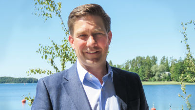 Thomas Blomqvist klädd i kostym står vid havet i Bromarv skärgårdshamn. I bakgrunden syns hav och träd. Han ler och tittar in i kameran.