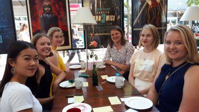 sex unga kvinnor sitter vid ett bord på en restaurang och tittar glatt in i kameran.