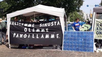 """Ett tält med en stor skyld där det står """"Vi ber om ursäkt för att vi bryr oss om dig"""" på finska."""