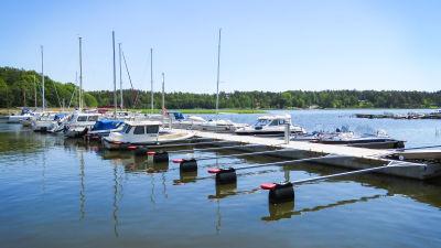 En brygga med båtar förtöjda vid bryggan. Soligt sommarväder.