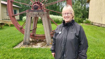 Kvinna står och ler mot kameran. Hon bär en svart jacka och glasögon.