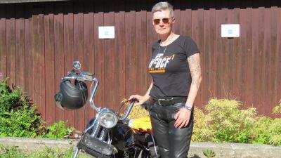 En kvinna med kort hår, solglasögon, svart t-shirt och läderbyxor står vid en motorcykel. Det är sommar och sol.
