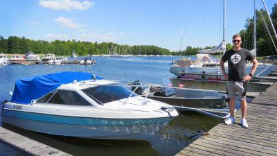 En ganska ung man står på en brygga bredvid sin motorbåt. I bakgrunden både motorbåtar och segelbåtar. Sommar och soligt.
