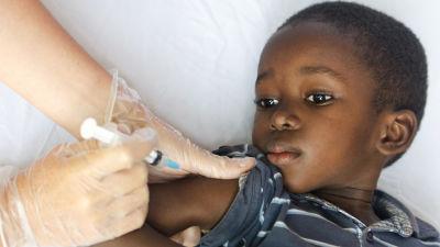 En liten pojke ligger på en säng och får vaccin i armen.