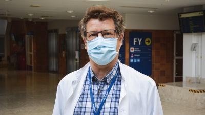 Medelålders man i läkarrock och munskydd står i en sjukhusaula och tittar in i kameran.