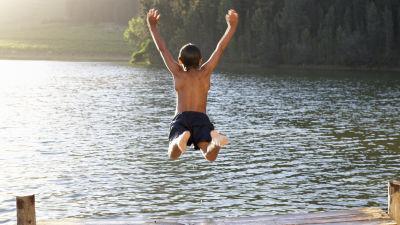 Pojke hoppar i en sjö