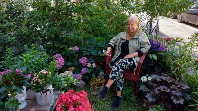 Margot Leinonen istuu taloyhtiön pihalle tekemässään puutarhassa Helsingin Punavuoressa.