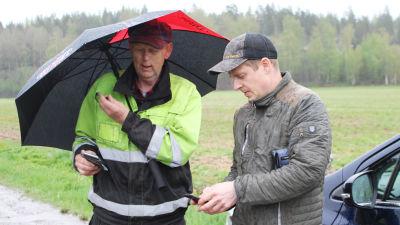 två jordbrukare ser på sina telefoner