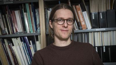 En leende man framför en bokhylla.