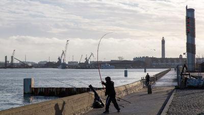 Ranskassa Calaisin satamassa kalastajia. Takana näkyy satama, mistä lähtee ja mihin tulee rahtilaivoja Isosta Britanniasta.