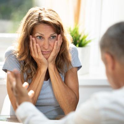 Bekymrad kvinna lyssnar på en man.