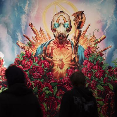 Människor går förbi en stor reklam för Bordelands spelet. På reklamen ses en person omringad av vackra röda rosor och vapen. Han har på sig en mask där ögonen lyser blåa.