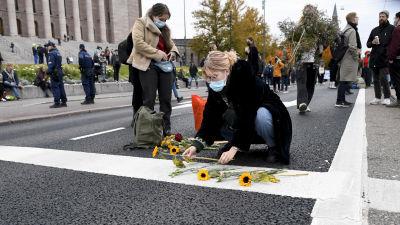 Elokapinaan osallistuva henkilö asettelee auringonkukkia Mannerheimintielle.