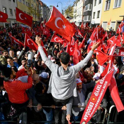 Turkin presidentin kannattajia heiluttamassa lippuja moskeijan edustalla Kölnissä.
