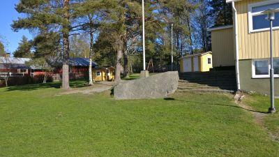 Gräsmatta med en stor sten på. I bakgrunden skymtar hus.