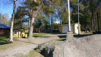 Gård på ett daghem. I förgrunden står en sten och en flaggstång. bakgrunden skymtar hus och träd.
