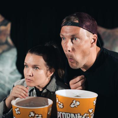 En man och en kvinna med popcornaskar i händerna följer spänt något med blicken.