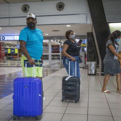 Resenärer som bär munskydd på Thambo International airport i Johannesburg i Sydafrika.