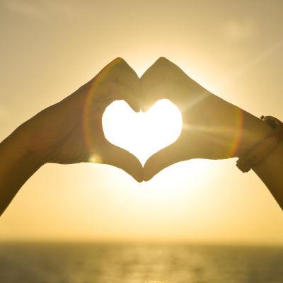 Två händer formar ett hjärta.
