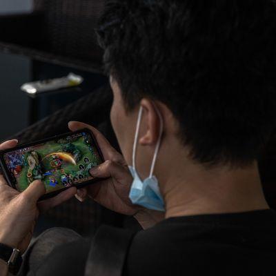 Mies pelaa huippusuosittua Honor of Kings -nettipeliä puhelimellaan Sanlitunissa Pekingissä. Verkkojätti Tencentin peliä pelaa keskimäärin 100 miljoonaa käyttäjää päivittäin ja se on yksi Kiinan suosituimmista..