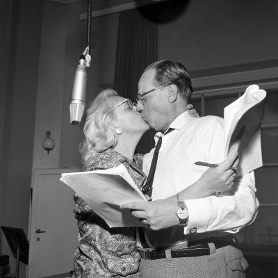 näytteljijät Ansa Ikonen ja Sasu Haapanen suukottelevat radiostudiossa käsikirjoitukset käsissään.