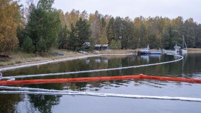 Vita och röda oljebommar ligger i vattnet vid strandbrynet.