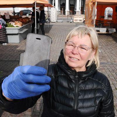 Torikauppias Tuula Matero näyttää, miten otetaan mom selfie Kauppatorilla syyskuussa 2020.