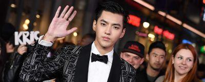 Unga man i kostym vinkar till kameran. Pop- och filmstjärnan Kris Wu i Los Angeles i januari 2017.