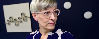 En blond korthårig kvinna i rosa glasögon.