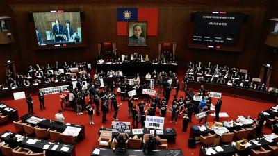 Cirka 20 personer står på golvet i det taiwanesisk parlamentets sessionssal och viftar med plakat. Taiwans första ledare Chiang Kai-shek blickar ned från ett porträtt på väggen bakom talarstolen.